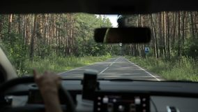 Woman driving empty country road through forest stock footage