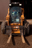 Woman driving Forklift. Caucasian woman in coveralls and hard hat driving a tractor forklift outside warehouse Royalty Free Stock Images