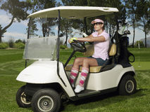 Woman Driving Golf Cart. Beautiful female golfer driving golf cart in course Royalty Free Stock Photography