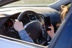 Woman driving her car as she reads an sms Royalty Free Stock Image