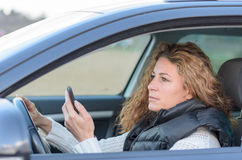 Woman is driving her car Stock Images