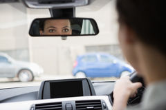 Woman driving with her reflection in the mirror Stock Photo