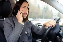 Woman driving his car and talking on the phone Stock Photography