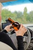 Woman driving holding a bottle of alcohol Stock Photo