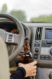 Woman driving holding a bottle of alcohol Royalty Free Stock Photo