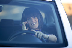 Woman driving holding a cellphone Stock Image