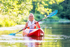 Woman driving with kayak on forest river. In summer Stock Photo