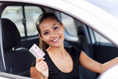 Woman driving licence. Cheerful young woman showing a driving licence she just got royalty free stock photography