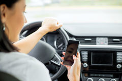 Woman driving and looking at cellphone Royalty Free Stock Image