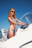 Woman driving a motor boat. Beautiful woman driving a motor boat Royalty Free Stock Images