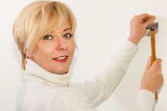 Woman is driving a nail into a wall Stock Photos
