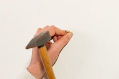 Woman is driving a nail into a wall Royalty Free Stock Images