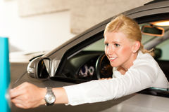 Woman driving out of a parking garage. Woman is driving out of a parking garage and is inserting the ticket into the barrier of the garage Royalty Free Stock Image