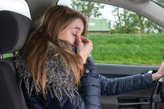 Woman driving overtired car and rubbing her eyes royalty free stock images