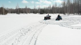Woman driving a quad bike around the man on the snow field. Woman driving a quad bike around the man on the snow field - Shot from drone stock video