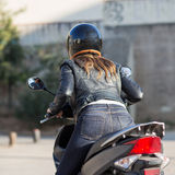 Woman driving a scooter royalty free stock image