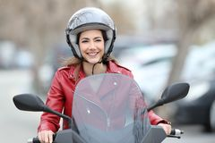 Woman driving a scooter on the street. Front view portrait of a happy woman driving a scooter on the street Stock Photos