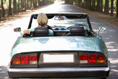 Woman driving sports car. Down country lane Stock Images