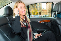 Woman driving in taxi, she is on the phone Royalty Free Stock Photos