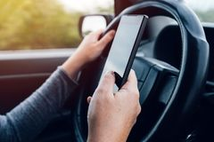 Woman driving and texting on mobile smartphone. While holding the steering wheel Royalty Free Stock Image