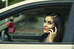 Woman driving to work holding cell phone. Royalty Free Stock Photography