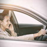Woman driving and using her smartphone Stock Photos