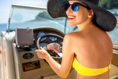 Woman driving yacht. Young and pretty woman in yellow skirt and swimsuit with hat and sunglasses driving luxury yacht in the sea royalty free stock image