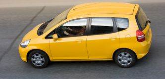 Woman driving yellow small car. A woman driving yellow car Royalty Free Stock Photo