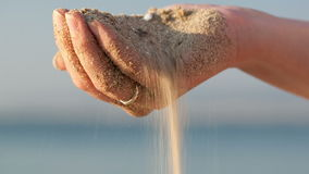 Woman drizzling sea sand through her fingers stock video