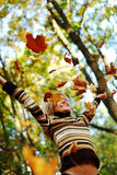 Woman drop leaves in autumn park. Woman drop up leaves in autumn park Stock Photo