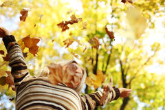 Woman drop leaves in autumn park. Woman drop up leaves in autumn park Royalty Free Stock Images