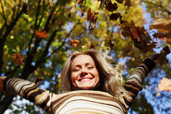 Woman drop leaves in autumn park Royalty Free Stock Image