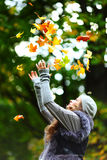 Woman drop leaves in autumn park. Woman drop up leaves in autumn park Royalty Free Stock Photos