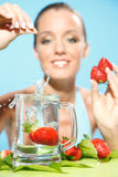 Woman drop strawberry into water Stock Photography