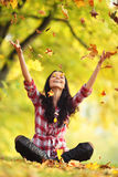 Woman drop up autumn leaves. Happy young woman drop up autumn leaves Royalty Free Stock Photos