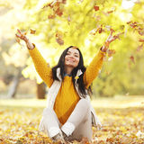 Woman drop up leaves. Siting in autumn park Royalty Free Stock Image