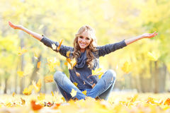 Woman drop up leaves. Sitting in autumn park Stock Photos