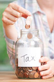 Woman Dropping Coins Into Jar Labelled Tax Stock Photo