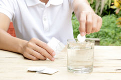 Woman dropping effervescent tablet in glass of water Stock Photos
