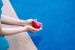 Woman dropping red heart in hands into the water. Closeup woman dropping red heart in hands into the water royalty free stock image