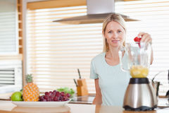 Woman dropping strawberry into the blender Royalty Free Stock Photo