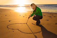 Woman drowing a heart shape in the sand. Stock Images