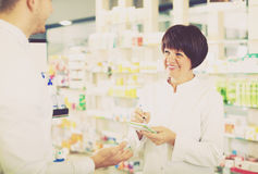 Woman druggist wearing white coat. Cheerful women druggist wearing white coat giving advice to customer in pharmacy Royalty Free Stock Image
