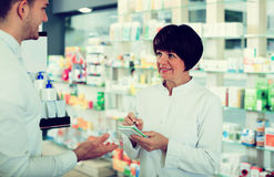 Woman druggist wearing white coat. Portrait of smiling women druggist wearing white coat giving advice to customer in pharmacy. Focus on the woman Royalty Free Stock Photography