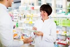 Woman druggist wearing white coat. Smiling women druggist wearing white coat giving advice to customer in pharmacy Stock Image