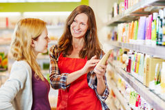 Woman in drugstore gets advice from saleswoman. While shopping for cosmetics stock image