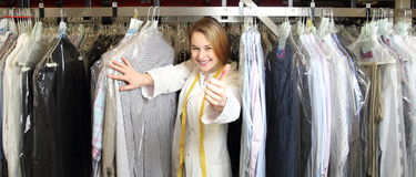 Woman in dry cleaning betwee shirts with thumb up Stock Photos