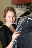 Woman in  Dry Cleaning with clothes packed in plastic foil Stock Images
