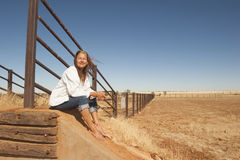 Woman on dry farm land in outback Australia. Portrait attractive mature woman sitting relaxed smiling at metal fence line in rural farming area in outback Royalty Free Stock Photography