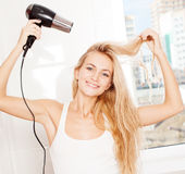 Woman dry hair hairdryer at bathroom Royalty Free Stock Image